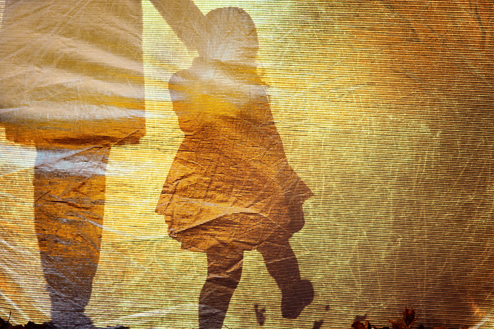 shadow of a little girl walking and holdings hands with an adult woman against a yellow background